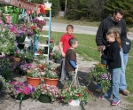 Jaydn Bennett (third from left), a member of the Wayne Township Future Farmers 4-H Club, helps with a flower basket selection during the club's 2014 spring plant sale. Shopping at the sale are (from left) Brady Harris, Brody Harris and Travis Harris, of Huntington, who purchased the flower basket; and club member Isaac Smelser.