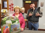 "Cathy (left), Andrea (middle) and Mark Krumanaker won the ""Spring"" basket for participating in the Andrews-Dallas Township Public Library's Winter Reading Club. Held throughout January and February, the club challenged families to track the total amount of time that they read. Eight baskets, each with a different theme, were awarded to participants."