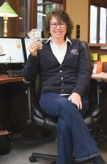 "Bippus State Bank employee Dawn Downs holds up her contribution for the ""Jeans Fund"" that raises money to give back to area organizations. Employees can wear jeans at work on Friday in exchange for a $2 donation."