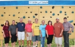 """Members of the Professional Piddlers Group, Huntington Township Advisory Board and the children of the late John Baker dedicate the climbing wall obstacle at the Lake Clare Fitness Park as the """"John Baker Memorial Climbing Wall"""" in his honor on Wednesday, July 10. Baker, a former Huntington Township Advisory Board member, donated funds to purchase the holds for the obstacle. Pictured are (from left) Huntington Township Advisory Board Secretary Tammy Kline; Township Board Member Carl Knowles; Township Board President Tim Guy; Stan Bippus, Bill Lucker and Dick Wymer, of the Professional Piddlers Group; Jennifer Miller, Baker's daughter; Mike Baker, Baker's son; and Jerry Martin of the Professional Piddlers Group."""