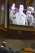 State Sen. Jim Banks (on video screen), who is serving in Afghanistan with the United States Navy, is sworn in as a state senator by Indiana Supreme Court Justice Robert Rucker (left).