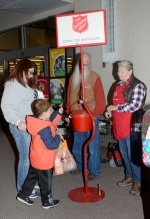 Chris Troxell (left) and her son, Trey, of Huntington, drop some money into the Salvation Army kettle at Owen's North on Friday, Nov. 24, while bell ringers Felix (third from left) and Deb Vanner look on. Friday was the first official day for the bell ringers in Huntington.
