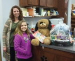 Renee (left) and Emily Perdue represent the Perdue Family team, which also included Cody and Ryan Perdue, as they collect the prize basket their family won in the Andrews-Dallas Township Public Library's winter reading program. Seventeen family teams signed up for the program, winning a ticket for the prize basket drawing for each hour read, with six prize baskets awarded.