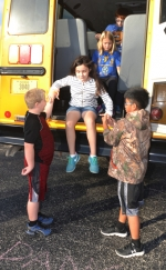 Lancaster Elementary School students Brody Bowers (left) and Cole Richison (right) help classmate Charleigh Rupert jump from the emergency door of a school bus, as Kaylee Krumanaker waits her turn to evacuate the bus. The evacuation drill was part of a school bus safety program presented at Lancaster on Monday, Oct. 17. The Huntington County Community School Corporation's Transportation Department is presenting the safety program at every HCCSC elementary school this week, with abbreviated programs set for the middle and high schools.