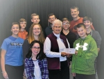 """Members of Union Church recently presented a check for $8,700.75 to Associated Churches for their """"By the Book"""" program. The money received was from the annual fish fry held at Union Church on Nov. 2. Celebrating the occasion are (front row) Bekah Bates; (middle row from left) Erika James, Danielle Gonser, Nancy Beaver and Wes Hotchkiss; and (back row from left) Nathan Williams, Will Hotchkiss, Bobby Schultz, Isaac Eckert, Jamie Hotchkiss and Jack Braden."""