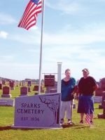 Sharon and Lonnie King stand with the new sign, memorial plaque and flagpole and flag at Sparks Cemetery, near Markle. Sharon King is a descendant of Soloman Sparks, who donated the original two acres for the cemetery, and she and her husband placed a memorial plaque in his honor.