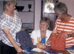 Women's Fellowship Service Director Gloria Wilson (left), of Central Christian Church, shows finished school kits to President Karen Farber (center) and Vice President Missy Schroeder.