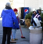 Yvonne Elzey (with broom) and Elisha Martin (with dustpan) sweep debris from the parking lot at the Andrews Dairy Store on Saturday, Nov. 6. The cleanup effort was coordinated by the Apostolic Grace Fellowship church in Andrews.