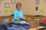 Sharon Rainwater, a volunteer at Love INC, sorts clothing for the organization's back-to-school program.