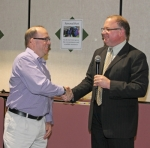 Huntington County Community School Corporation Director of Technology Tom Ashley (left) is congratulated by HCCSC Superintendent Randy Harris at the school board meeting on Monday, May 9, after Ashley was named to the Consortium of School Networking (COSN) Hall of Fame.