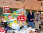 Rev. Tim Anderson, pastor of St. Peter Lutheran Church, and church members Pam Wertenberger and Barba Eickhoff (from left) stand in the midst of the diapers stacked up in the Bare Necessities diaper store housed in the church's educational building. The diapers are available twice a month to families who register through Love In the Name of Christ.