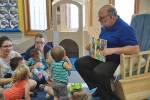 Huntington Mayor Brooks Fetters reads a story to an Early Head Start class at Pathfinder Kids Kampus on Community Reading Day, Thursday, May 18, in celebration of Head Start's 52nd birthday. P