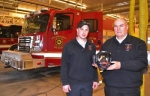 Firefighter Brandon Bolinger (left) and Chief Tim Albertson stand in front of the Huntington Fire Department's newest fire truck as they display the air masks now being used by Huntington firefighters. The masks have built-in thermal imaging cameras, allowing firefighters to search a room for heat sources that will indicate the location of a person or of flames. Previously, firefighters used hand-held thermal imaging cameras. The new equipment allows their hands to remain free to make a rescue or handle firefighting equipment.