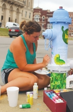 "Alex Stanley, of Warren, paints a mural with the theme of ""A Bug's Life"" at the corner Warren and Court streets in Huntington on Friday, July 24. This is the sixth time that Stanley has participated in the LaFontaine Arts Council hydrant painting project."
