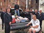 Huntington firefighters deliver a truckload of pork sausage to Bob Burnsworth (front) for use at the New Life Fellowship Community Food Ministry on Thursday, May 15.