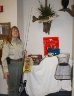 Laura Whiteleather, an interpretive naturalist at the Interpretive Center at Salamonie Reservoir, displays some of the donated prizes for the area reservoir's youth fishing derbies to be held June 7.