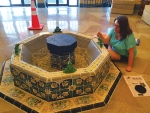 LaFontaine Center manager Rose Meldrum touches up deteriorated tiles on the frog fountain in the center's lobby. The fountain has been restored in time for the LaFontaine Center's 30th anniversary.