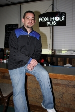 Lee Cutting, co-owner of Norwood Golf Course, in Huntington, sits in Norwood's new bar and grill, Foxhole Pub, located in the former Elks Club building, which also contains a newly-installed golf simulator.