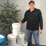 Matt East, co-owner of Fusion Chemical, stands by containers of hand sanitizer produced by his Huntington company, which is a metalworking fluids manufacturer, but has recently reoriented parts of its production to make sanitizer – a product that has been in high demand during the COVID-19 pandemic.