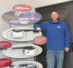 Nick Yarger stands next to a garage door and a display in the showroom of Garage Door Services of Huntington, which has a new location at 102 N. Briant St., Huntington. The move allows for the entire business to be located at one place.