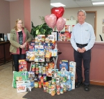 """Kelley Miller (left), assistant director of  Love In the Name of Christ and Dr. Stephen Geders stand amid donations provided by Huntington Chiropractic Center's patients and staff during the clinic's annual """"Spread the Love for Love INC Day"""" event."""