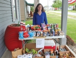 Emily Smith, an agent at Larson Insurance LLP, stands behind the giving table located outside the agency's office, at 1639 N. Jefferson St., Huntington. The table is stocked with both food and non-food items Monday through Friday from 9 a.m. to 5 p.m. and on Saturday from 9 a.m. until noon.