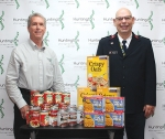 """Dr. Stephen Geders (left) of the Huntington Chiropractic Center and Capt. Dennis Marak of the Huntington Salvation Army display food already collected for the chiropractic center's """"Salvation Army Day"""" event. The donations will go to the Salvation Army's food pantry to help provide meals for area residents through the summer."""