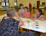 Sibings Baden (left) and Alexandra (center) Craig, along with mom Tiffany Craig, chat with teacher Rita Disler during registration day at Huntington Catholic School on Wednesday, Aug. 6.