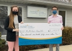 Health Educator of McMillen Health Allie Mortensen (left) receives a check from HCCF Executive Director Matt Ditzler to purchase props for their education programs on nutrition and drug prevention.