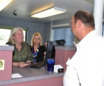 Sherri Bannister (left), member service representative, and Kathy Borskey, manager of the Huntington County Federal Credit Union, handle a transaction with Ralph Matchett, a member of the credit union's board of directors.