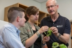 Huntington University students Adam Konger (left) and Shawna Miller (center) listen as Dr. Raymond Porter, director of the Haupert Institute for Agricultural Studies, explains the different parts of a young soybean plant. The program will get a second greenhouse with the help of a grant from DuPont Pioneer.