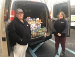 Maintenance Tech Mike Freel (left) and Area Manager Lisa Pavey of Hauenstein Hills apartments show the donations of food collected by the apartment complex's residents before they leave to drop it off at Love INC.
