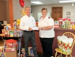 Amid a sea of donated groceries, Dr. Stephen Geders (left), of Huntington Chiropractic Center, adds to the Salvation Army's food pantry with a monetary gift of $700, presented to Maj. Normalene Daniels, of the Huntington Salvation Army location. The donations were collected through a fund-raiser and contributed by patients and staff of the center.
