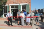 Sara Wilcox (fifth from left) cuts the ribbon to declare HomeCraft – The Art of Home officially open to the public on Saturday, Aug. 22, outside the front door of the building she and her husband, Matt Wilcox (sixth from left) purchased this year. Celebrating the occasion are (from left) Huntington Mayor Richard Strick, Paul Smelser, store co-owner Ronda Smelser, Huntington City Councilman Charles Chapman, Sara Wilcox, Matt Wilcox and Huntington City Councilman Joe Blomeke.