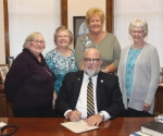 Members of the Huntington County Homemakers Extension Board flank Huntington Mayor Brooks Fetters (seated), as he prepares to sign a proclamation naming Oct. 20 through Oct. 26 as Indiana Extension Homemakers Week in the City of Huntington. Celebrating the occasion are (from left) Carla Rice, Stephanie Jerabek, Rita McCabe and Nancy Vickery.