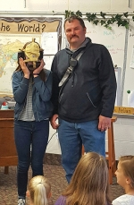 Huntington Firefighter Greg Shearer watches as Roanoke Elementary School fifth-grader Sophie Riggers tries on his thermal imaging camera. The class is raising money to buy another device for the department.