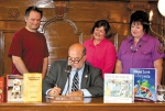 Surrounded by books, Huntington Mayor Brooks Fetters signs a proclamation on Wednesday, Aug. 27, designating Sept. 7 as Read a Book Day.