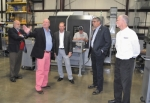 Troy Johnson (center), president of Incipio Devices, and Mike Wack (right), the company's vice president of development, provide a tour of the Commercial Road facility to (from left) Huntington Mayor Brooks Fetters and Huntington County Commissioners Larry Buzzard and Tom Wall after announcing a major business expansion on Friday, Oct. 27. An unidentified employee is working in the background.