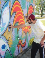 "James Allen Mitten, artistic alias ""ey3zlo,"" puts the finishing touches on his interactive mural at Lake Clare park."