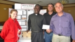 Rev. Sebastian Twinomugabi (second from left) received some local support to assist in reactivating his brick factory when he returns to Uganda in July. Jessica Hartmus (left) designed a non-electric roller system to make the materials easier to move; both she and the local Knights of Columbus council also made monetary donations. Representing the council are Deputy Grand Knight Dave Bowman (second from right) and Grand Knight Jeff Scher (right).