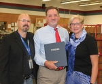 Huntington Postmaster Dave Kuehnert (center) holds the certificate presented to him on Friday, Oct. 2, as he officially retires from the United States Postal Service. He is flanked by his supervisor, Todd Mansker (left), manager of post office operations, and his wife, Karen.