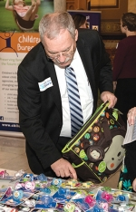 "State Rep. Dan Leonard (R-Huntington) donates a new diaper bag filled with baby supplies for an Indiana foster family during the ""Bags of Hope"" event on Wednesday, Jan. 24, at the Statehouse in Indianapolis."