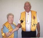 """Joyce Walker (left) outgoing president ofhte Andrews Lions Club, passes the gavel to new President Othel """"Slim"""" Fouts."""