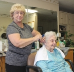 Lora Gamble (left) puts the finishing touches on resident Mary Jane Kline's coiffure Wednesday, Sept. 13, at Miller's Merry Manor. Gamble has worked in three different types of jobs at the building, since it was first owned by Friendly Nursing Home.