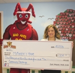The Fort Wayne Mad Ants mascot presents a check for $1,204 to Jessica Broyles (right) of McKenzie's Hope Child Advocacy Center after the organization won the team's Mad Ants Community Challenge contest.