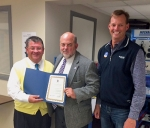 Huntington Mayor Brooks Fetters (center) holds the proclamation he and Huntington County Commissioner Tom Wall jointly signed  establishing October as Manufacturing Month in both the City of Huntington and Huntington County. Celebrating the occasion are Mark Wickersham (left), executive director of Huntington County Economic Development, and Michael Zahn, president of the Lime City Committee.