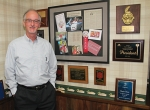 Steve Mason, of Insurance Services, stands in his office beside the wall of plaques and accolades he has received over the years, most of them for his volunteerism in the Huntington community. Mason will retire from the company in December.