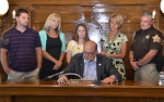 Huntington Mayor Brooks Fetters (seated) reads a proclamation designating this week, Sept. 8 through Sept. 15, as Suicide Prevention Week in Huntington.