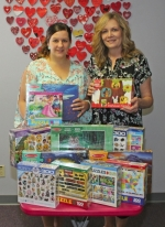 Jessica Broyles (left), executive director of McKenzie's Hope, receives a supply of children's puzzles from Chris Walker, manager of the Indiana Dream Center Thrift Store, on Monday, June 12. About 300 puzzles were provided by the Indiana Box Company.