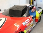 """Chad Wiegmann, manager of the Men's Mart store in Roanoke, sits in a genuine NASCAR race car that is in the process of being turned into a virtual reality (VR) game. The store features different types of arcade games and other """"man cave"""" type items."""